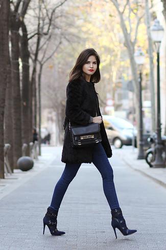 Comment porter: manteau de fourrure noir, jean skinny bleu, bottines en daim bleu marine, cartable en cuir noir