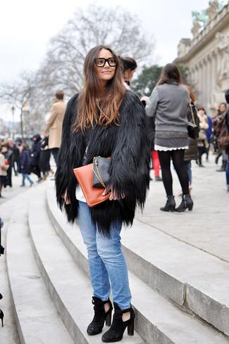 Comment porter: manteau de fourrure noir, t-shirt à col rond imprimé blanc et noir, jean bleu clair, bottines en daim découpées noires