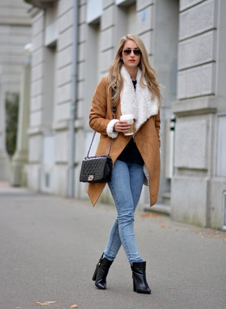 Associer un manteau en peau de mouton retournée brun clair avec un jean skinny bleu clair est une option confortable pour faire des courses en ville. Cette tenue se complète parfaitement avec une paire de des bottines en cuir noires.
