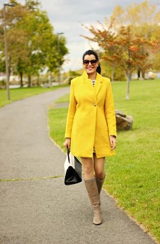 Comment porter: manteau jaune, bottes hauteur genou en cuir marron clair, cartable en cuir blanc et noir