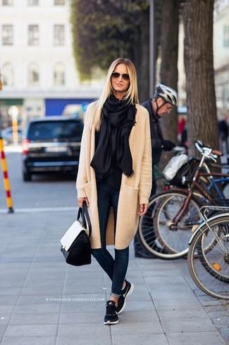 Comment porter: manteau beige, jean skinny bleu marine, chaussures de sport bleu marine, cartable en cuir noir et blanc