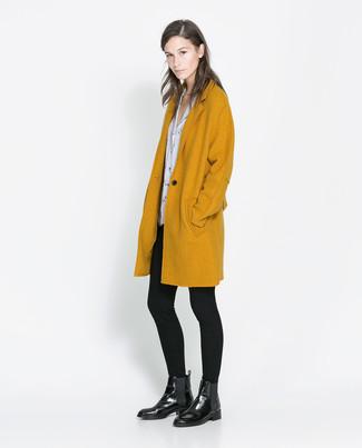 Comment porter: manteau moutarde, chemisier à manches courtes imprimé blanc et noir, leggings noirs, bottines chelsea en cuir noires