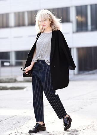 Comment porter: manteau noir, t-shirt à col rond gris, pantalon de costume à rayures verticales bleu marine, mocassins à pampilles en cuir noirs