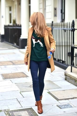 Comment porter: manteau marron clair, pull à col rond imprimé vert foncé, leggings en denim bleu marine, bottines en cuir marron