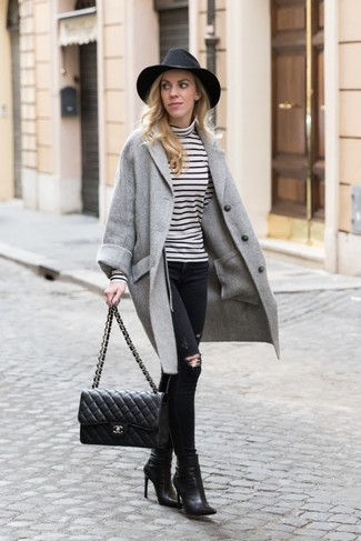 Comment porter: manteau gris, pull à col roulé à rayures horizontales blanc et noir, jean skinny déchiré noir, bottines en cuir noires
