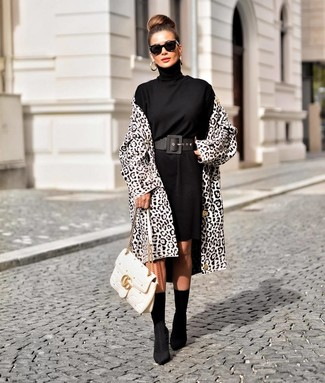 Comment porter des bottines élastiques noires: Essaie d'harmoniser un manteau imprimé léopard blanc et noir avec une robe-pull noire pour un déjeuner le dimanche entre amies. Assortis ce look avec une paire de des bottines élastiques noires.