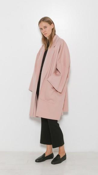 Tendances mode femmes: Opte pour un manteau rose avec un pantalon flare noir si tu recherches un look stylé et soigné. Cette tenue se complète parfaitement avec une paire de des slippers en cuir noirs.