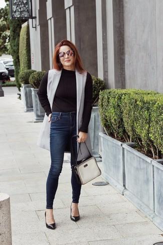 Comment porter: manteau sans manches gris, pull à col rond noir, jean skinny bleu marine, escarpins en cuir noirs