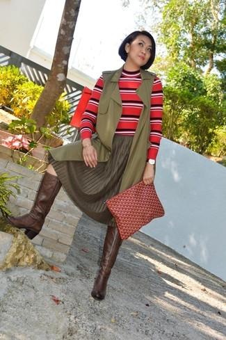 Comment porter: manteau sans manches olive, pull à col rond à rayures horizontales orange, jupe mi-longue plissée olive, bottes hauteur genou en cuir marron foncé