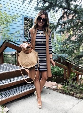 Comment porter: manteau sans manches marron, robe droite à rayures horizontales noire et blanche, sandales compensées en cuir marron clair, sac fourre-tout de paille marron clair