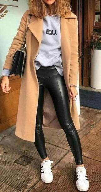 Comment porter des leggings en cuir noirs: Essaie d'associer un manteau marron clair avec des leggings en cuir noirs et tu auras l'air d'une vraie poupée. Une paire de des baskets basses en cuir blanches et noires est une option génial pour complèter cette tenue.