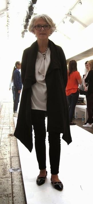 Comment s'habiller après 60 ans: Harmonise un manteau noir avec un pantalon slim noir pour prendre un verre après le travail. Cette tenue est parfait avec une paire de des slippers en cuir noirs.