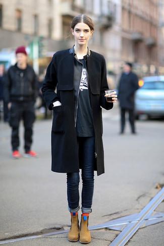 Comment porter: manteau noir, veste motard en cuir noire, t-shirt à col rond imprimé noir et blanc, jean skinny bleu marine