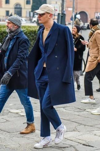 Comment porter un costume à rayures verticales bleu: Essaie de marier un costume à rayures verticales bleu avec un pardessus bleu marine pour un look classique et élégant. Jouez la carte décontractée pour les chaussures et complète cet ensemble avec une paire de des baskets basses en cuir blanches.