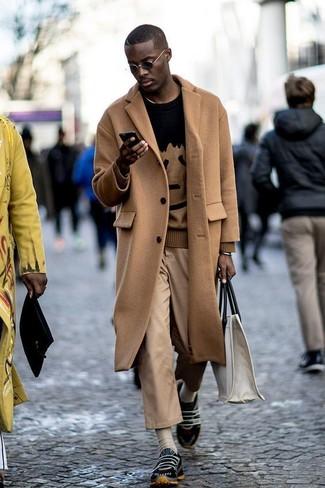 Comment porter: pardessus marron clair, pull à col rond imprimé noir, pantalon chino marron clair, chaussures de sport noires