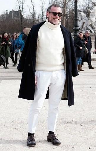 Comment porter: pardessus noir, pull à col roulé blanc, pantalon chino blanc, chaussures derby en cuir marron foncé