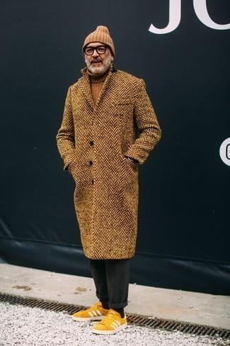 Comment porter un pantalon chino en laine gris foncé: Harmonise un pardessus à chevrons marron clair avec un pantalon chino en laine gris foncé pour achever un look habillé mais pas trop. Jouez la carte décontractée pour les chaussures et choisis une paire de des baskets basses en daim jaunes.