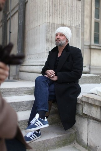 Comment s'habiller après 50 ans: Opte pour un pardessus noir avec un jean bleu marine pour un look idéal au travail. Si tu veux éviter un look trop formel, fais d'une paire de des baskets basses en daim bleu marine et blanc ton choix de souliers.