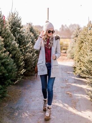 Comment porter: parka grise, chemise de ville écossaise rouge, jean skinny bleu marine, bottes d'hiver en daim marron
