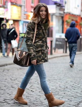 Comment porter: parka camouflage olive, jean skinny bleu clair, bottes ugg marron, grand sac en cuir imprimé marron foncé