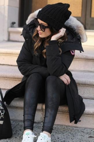 Comment porter: parka noire, leggings en cuir noirs, baskets basses en cuir blanches, sac fourre-tout en cuir noir