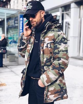 Comment porter: parka camouflage olive, sweat à capuche noir, jean skinny noir, casquette de base-ball imprimée noire et blanche