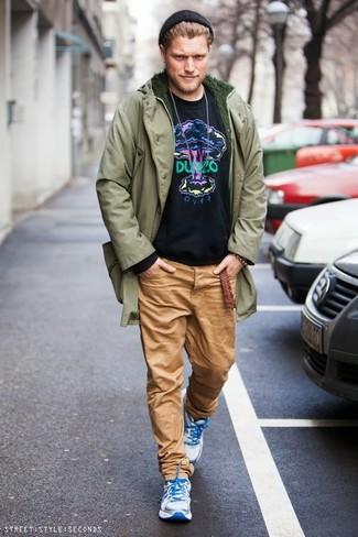 Comment porter: parka olive, sweat-shirt imprimé noir, pantalon chino marron clair, chaussures de sport blanches