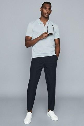 Tendances mode hommes: Opte pour un polo blanc avec un pantalon chino noir pour une tenue idéale le week-end. Cette tenue est parfait avec une paire de des baskets basses en cuir blanches.