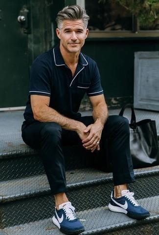 Comment porter un pantalon chino noir: Associe un polo bleu marine avec un pantalon chino noir pour un look de tous les jours facile à porter. Si tu veux éviter un look trop formel, complète cet ensemble avec une paire de des chaussures de sport bleu marine.