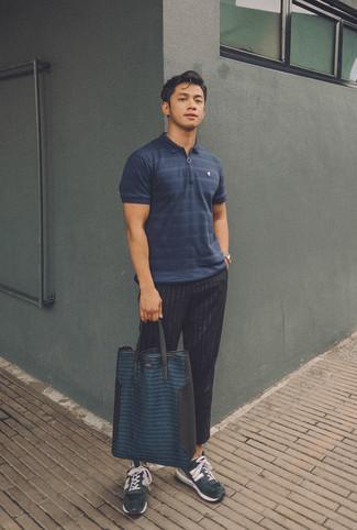 Comment porter: polo à rayures horizontales bleu marine, pantalon de costume à rayures verticales noir, chaussures de sport en daim bleu marine, sac fourre-tout en cuir bleu marine