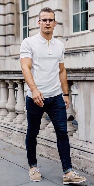 Comment porter un jean bleu marine: Marie un polo blanc avec un jean bleu marine pour une tenue confortable aussi composée avec goût. Cette tenue se complète parfaitement avec une paire de chaussures bateau en toile marron clair.