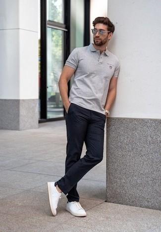 Comment porter un pantalon chino bleu marine: Pour une tenue de tous les jours pleine de caractère et de personnalité harmonise un polo gris avec un pantalon chino bleu marine. Cette tenue est parfait avec une paire de des baskets basses en toile blanches et noires.