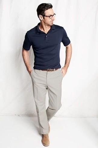 Comment s'habiller après 40 ans: Porte un polo bleu marine et un pantalon chino gris pour un déjeuner le dimanche entre amis. Habille ta tenue avec une paire de bottines chukka en daim marron clair.
