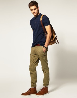 Comment porter: polo bleu marine, pantalon chino olive, bottines chukka en cuir marron, sac à dos en toile marron clair