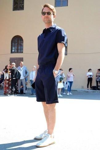 Tendances mode hommes: Choisis un polo bleu marine et un short bleu marine pour une tenue idéale le week-end. Complète ce look avec une paire de des baskets basses en toile blanches.