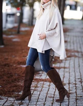 Comment porter: poncho beige, jean skinny bleu, bottes hauteur genou en daim marron foncé, sac fourre-tout en cuir beige