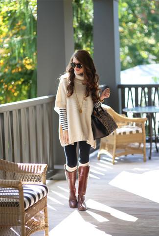 Comment porter: poncho beige, pull à col rond à rayures horizontales blanc et bleu marine, leggings noirs, bottes hauteur genou en cuir marron