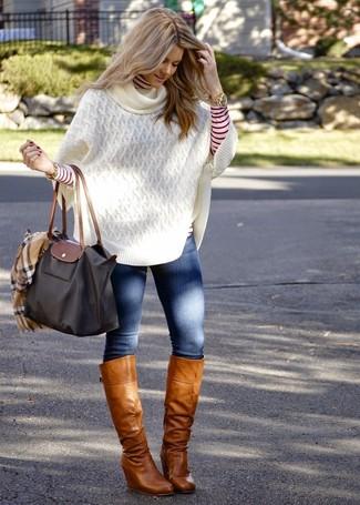 Comment porter: poncho en tricot blanc, pull à col roulé à rayures horizontales rouge et blanc, jean skinny bleu, bottes hauteur genou en cuir marron clair