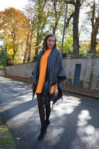 Associe un poncho gris avec une robe droite orange pour obtenir un look relax mais stylé. Cette tenue est parfait avec une paire de des bottines en daim noires.