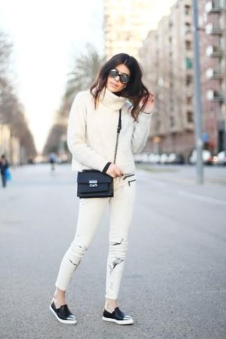 Comment porter: pull à col boule blanc, jean skinny imprimé blanc, baskets à enfiler en cuir noires, sac bandoulière en cuir noir