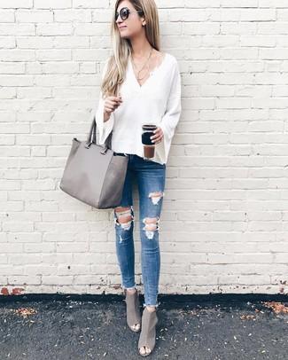 Comment porter: pull à col en v blanc, jean skinny déchiré bleu, bottines en cuir découpées grises, sac fourre-tout en cuir gris