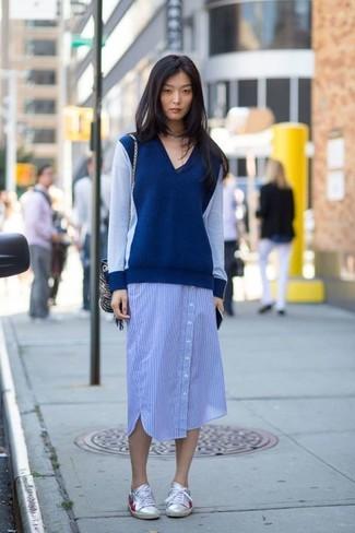 Comment porter: pull à col en v bleu marine, robe chemise à rayures verticales bleue, baskets basses en cuir argentées