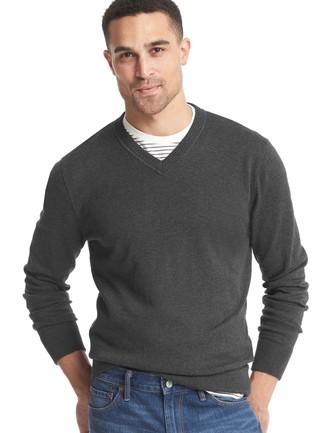 Associe un pull à col en v gris foncé avec un jean bleu pour une tenue confortable aussi composée avec goût.
