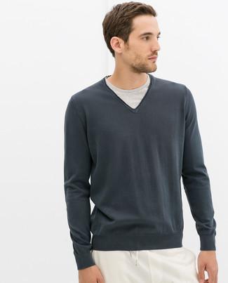 Associer un pull à col en v gris foncé avec un pantalon de jogging blanc est une option confortable pour faire des courses en ville.
