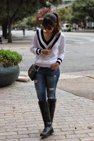 Comment porter: pull à col en v blanc et noir, jean skinny déchiré bleu marine, bottes hauteur genou en cuir noires, sac bandoulière en cuir noir