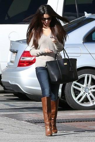 Tenue de Selena Gomez: Pull à col en v gris, Jean skinny bleu marine, Bottes hauteur genou en cuir marron, Sac fourre-tout en cuir noir