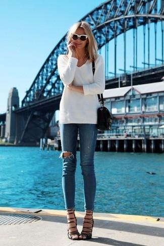 Comment porter: pull à col en v blanc, jean skinny déchiré bleu, sandales à talons en daim noires, sac bandoulière en cuir noir