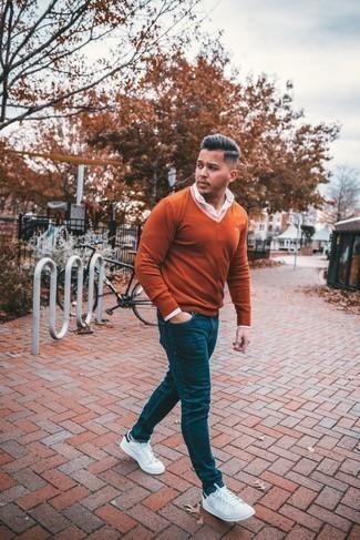 Comment porter un jean bleu marine: Marie un pull à col en v orange avec un jean bleu marine pour une tenue confortable aussi composée avec goût. Cette tenue se complète parfaitement avec une paire de baskets basses en cuir blanc et bleu marine.