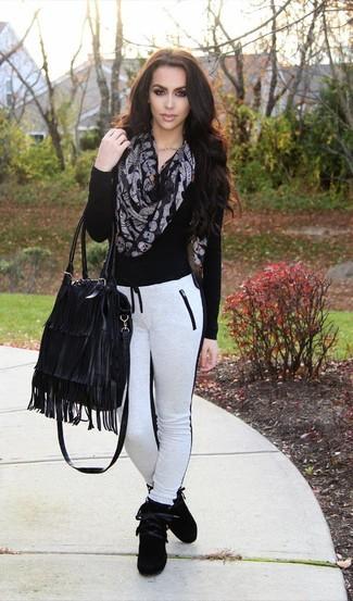 Comment porter: pull à col en v noir, pantalon de jogging blanc et noir, baskets montantes en daim noires, sac fourre-tout en cuir à franges noir