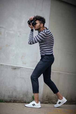 Comment porter: pull à col rond à rayures horizontales blanc et noir, pantalon chino noir, baskets basses en cuir blanches